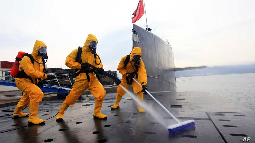 In this photo taken on July 17, 2013 and released by the Chinese Navy Oct 27, 2013, sailors in protective gear clean and disinfect a nuclear submarine during a drill at the Qingdao submarine base in east China's Shandong province.