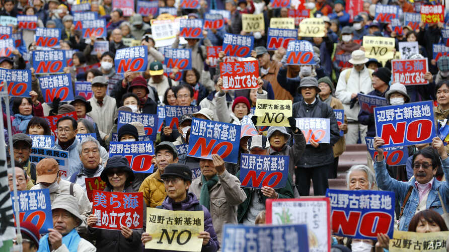 """FILE - Anti-U.S. base relocation protesters hold placards with a slogan that reads: """"No to Henoko new base"""" during a rally in Tokyo, Nov. 29, 2015, as they show their strong support to Okinawans after the Japanese government took the local government"""