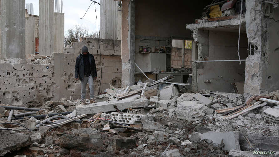 A man inspects a damaged house after an airstrike on al-Yadouda village, in Daraa Governorate, Syria, Feb. 15, 2017.