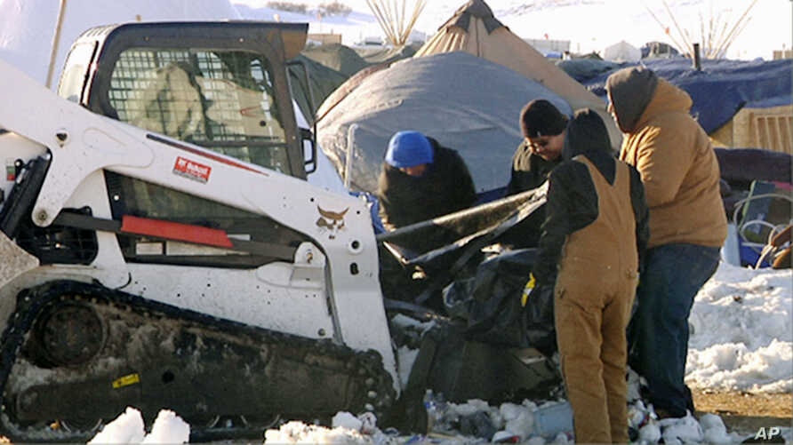 FILE - A photo from video provided by KXMB in Bismarck, N.D., shows cleanup beginning at a North Dakota encampment near Cannon Ball where Dakota Access oil pipeline opponents have protested for months.