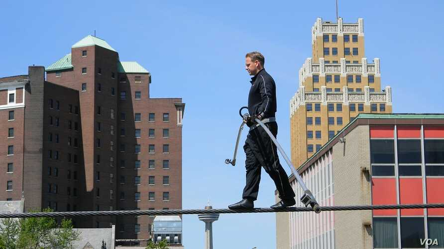 Nik Wallenda, on a wire three meters above a mostly empty parking lot, practices for his tightrope walk across Niagra Falls. (D. Robison/VOA)