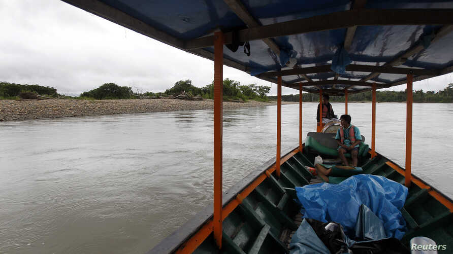 Boaters look at a beach where several uncontacted indigenous people have been spotted in recent years, near Diamante, a town in the Alto Madre de Dios River, Peru, May 26, 2014.