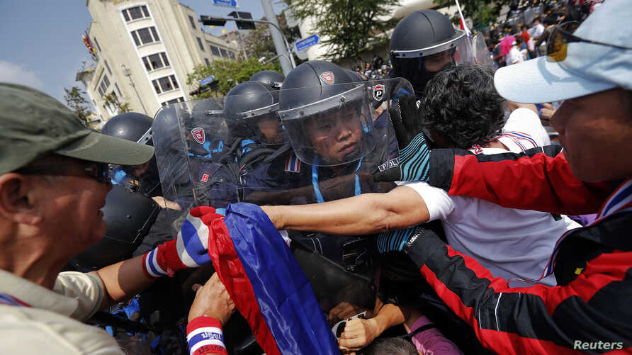 Policemen charge against anti-government protesters at one of their barricades near the Government House in Bangkok February 18, 2014. A Thai police officer was killed and dozens of police and anti-government protesters were wounded in gun battles an