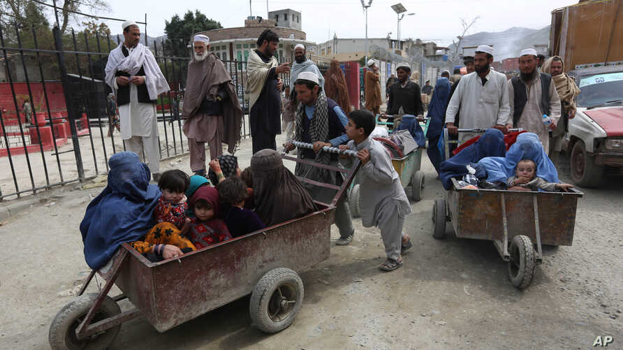 FILE - Afghan women and children sit in a cart pushed by a man as they enter Afghanistan through Pakistan's border crossing in Torkham, east of Kabul, Afghanistan, March. 11, 2015.