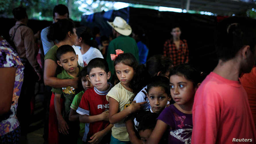 Children line up at dinner time at a shelter for displaced people from El Castano village in the town of Caluco, El Salvador, Sept. 26, 2016.