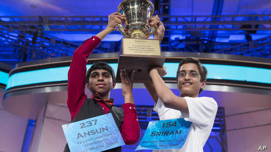 Ansun Sujoe, 13, of Fort Worth, Texas, left, and Sriram Hathwar, 14, of Painted Post, N.Y., raise the championship trophy after being named co-champions of the National Spelling Bee, on Thursday, May 29, 2014.