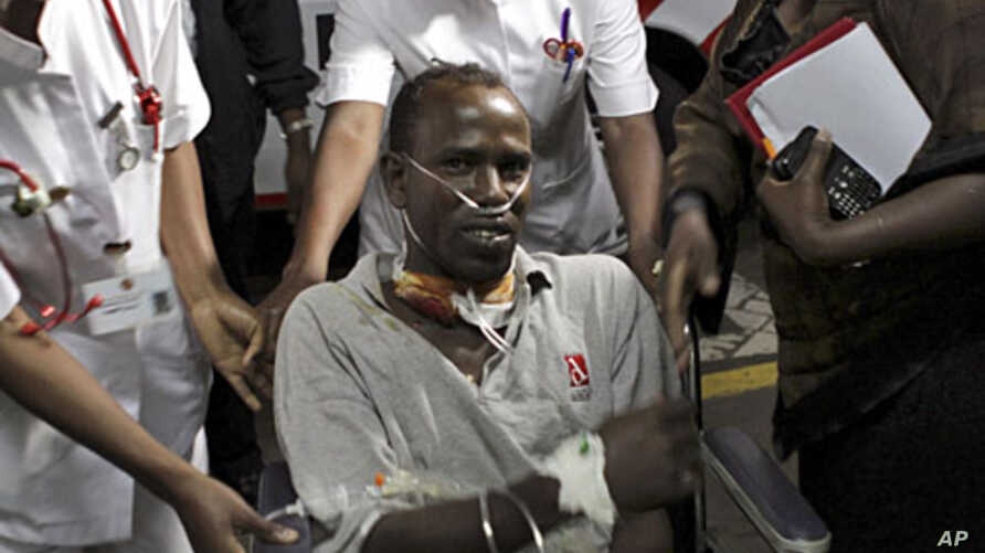 An unidentified Medecins Sans Frontieres (MSF) driver is assisted from an ambulance as he arrives at the Nairobi hospital in Kenya's capital Nairobi, October 13, 2011