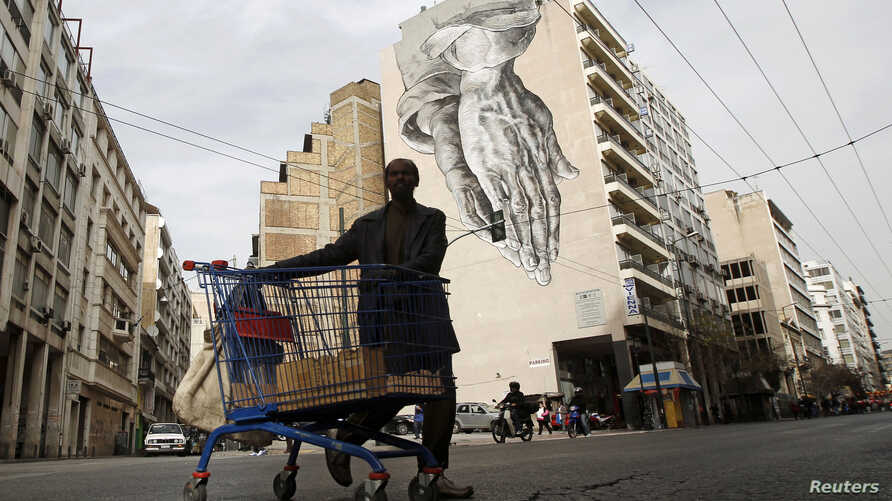 FILE - An immigrant living in Greece pushes a shopping trolley with scrap in front of a building covered with street art in Athens.
