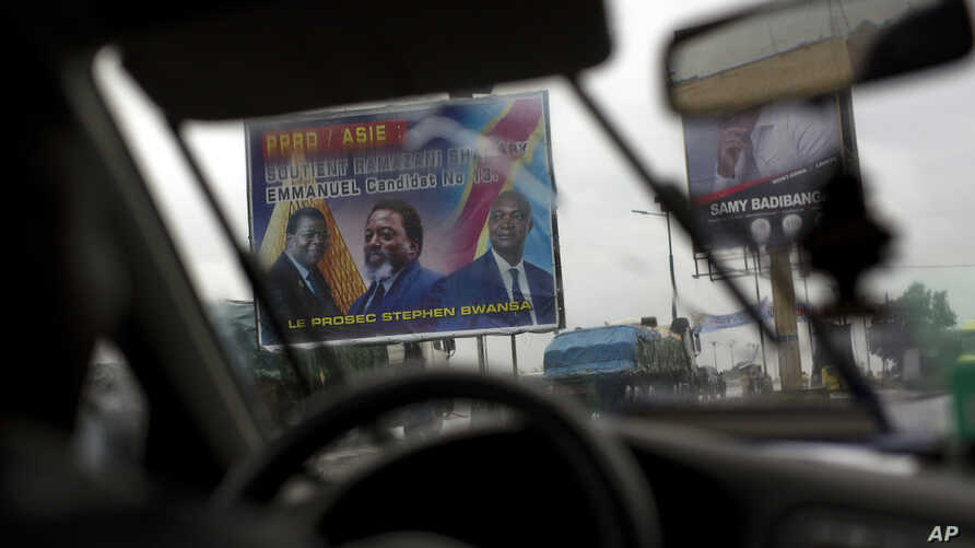 A poster featuring Congo's current President Joseph Kabila with ruling party candidate and former interior minister Emmanuel Ramazani Shadary is displayed on the road leading to the airport in Kinshasa, Democratic Republic of the Congo, Dec. 17, 2018