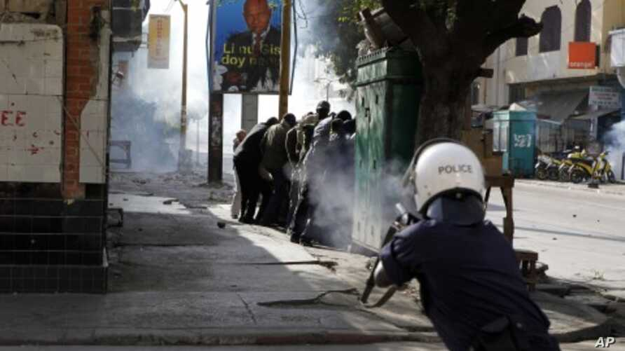 A police officer fires tear gas at close range directly into a group of anti-government protesters sheltering behind a kiosk, on a central boulevard in Dakar, Senegal, February18, 2012.
