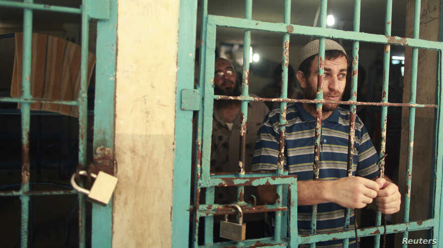 A Palestinian inmate stands behind the bars of a Hamas-run jail in Gaza City after prayers during the holy month of Ramadan, July 23, 2012.