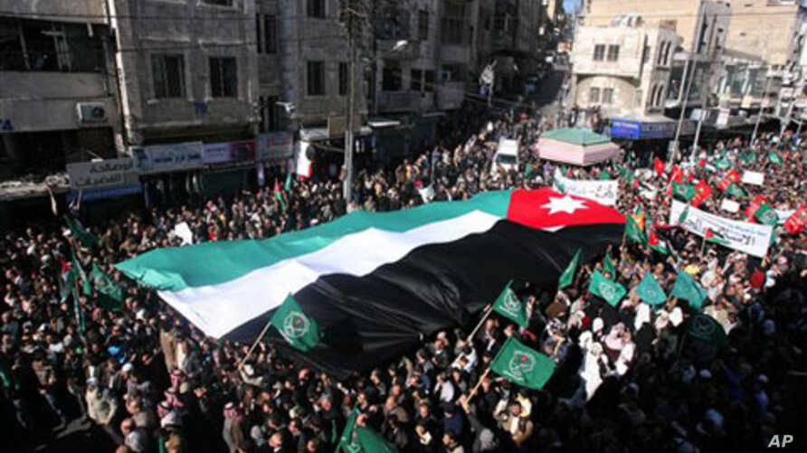 Jordanian protesters hold a giant national flag, as they march during a protest demanding the resignation of the prime minister and his government over price increases and inflation, in Amman, 21 Jan 2011