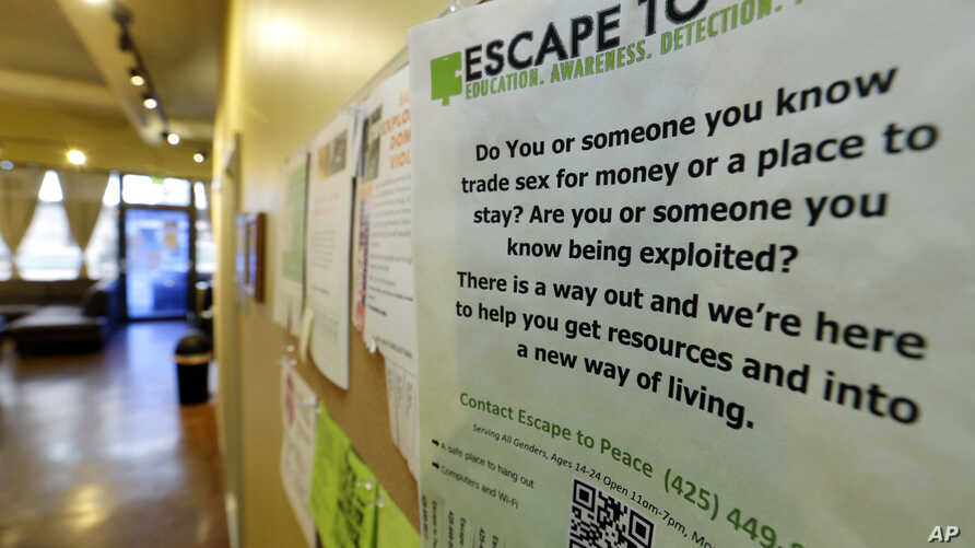 FILE - A poster on the wall of a drop-in center for victims of sex trafficking in SeaTac, Washington, refers victims to a similar program at different location, Feb. 27, 2017.
