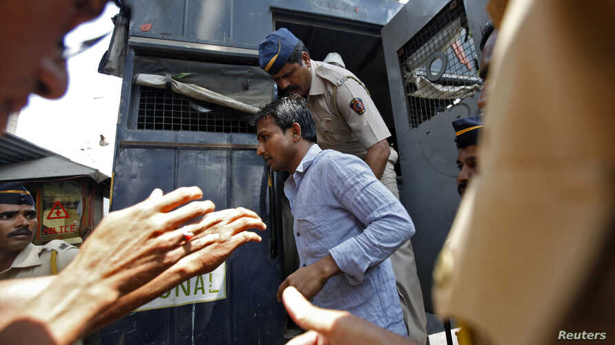 Policemen escort one of the four men convicted of raping a photojournalist outside a jail in Mumbai, March 20, 2014.