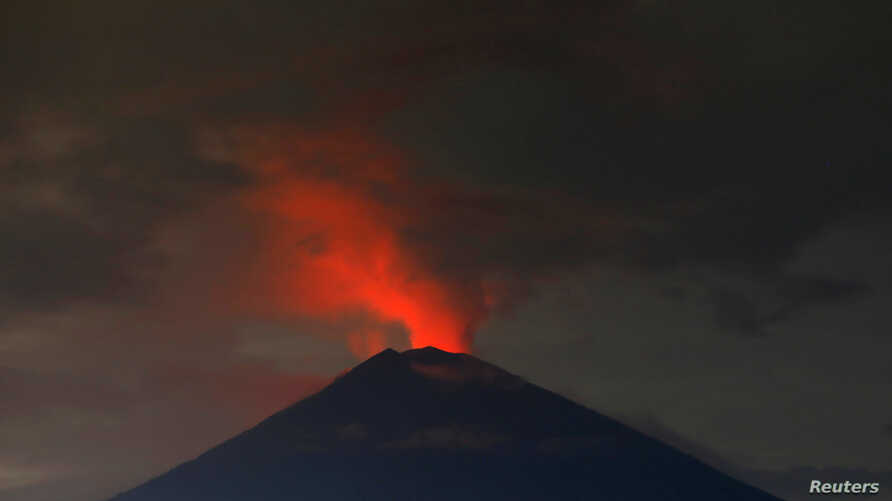 Lava, inside the crater of Mount Agung, reflects off the volcano's ash and clouds, while it erupts, as seen from Amed, Karangasem Regency, Bali, Indonesia, Nov. 30, 2017.