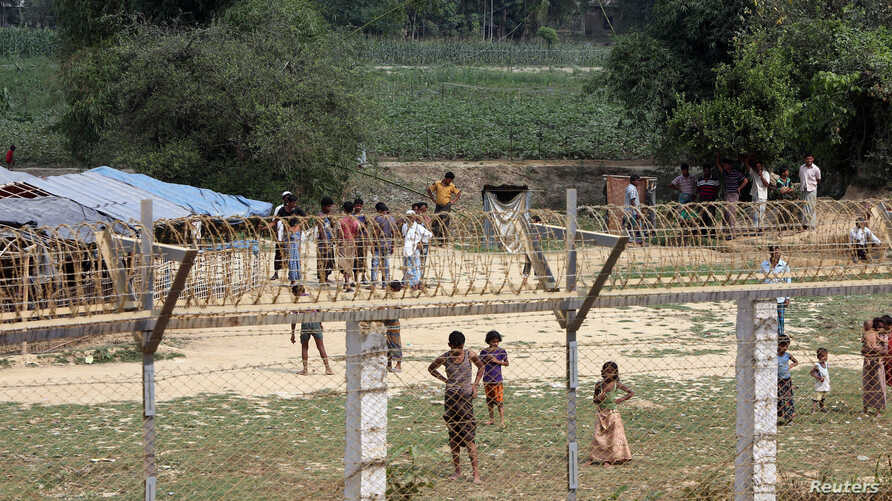 Rohingya people who fled from their towns after the violence in the state of Rakhine, are seen behind a fence on the border line outside Maungdaw, Myanmar, March 31, 2018.