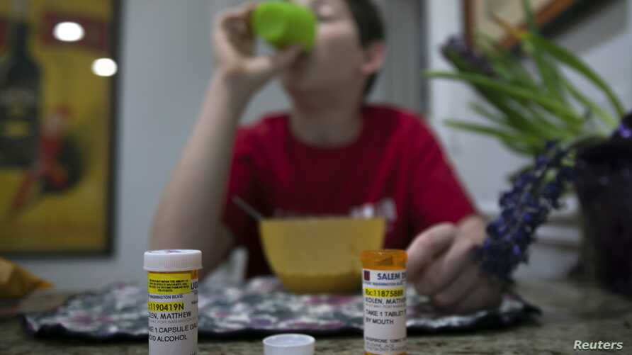 A youngster diagnosed at age eight with Asperger's syndrome takes medication with his breakfast at home on Long Island, New York, March 30, 2012.