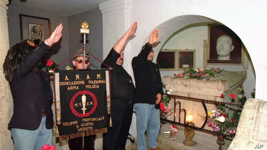 FILE - A small group of fascist supporters gives the Roman salute in front of the tomb of late dictator Benito Mussolini in Predappio, central Italy, April 28, 1995, on the occasion of the 50th anniversary of Mussolini's death. The new bill in Italy