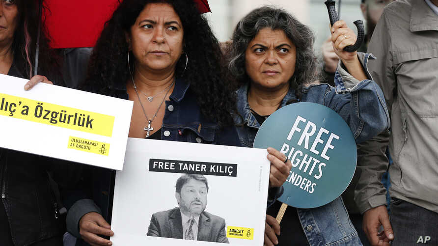 Human rights activists stage a protest outside a court where eleven human rights activists, among them Amnesty International's Turkey chairman Taner Kilic, are on trial, accused of belonging to and aiding terror groups, in Istanbul, Turkey, Oct. 25,