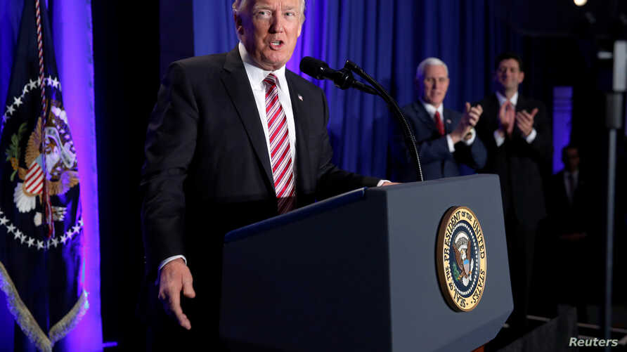 U.S. President Donald Trump is applauded by Vice President Mike Pence and House Speaker Paul Ryan as he arrives to speak at a congressional Republican retreat in Philadelphia, Jan. 26, 2017.