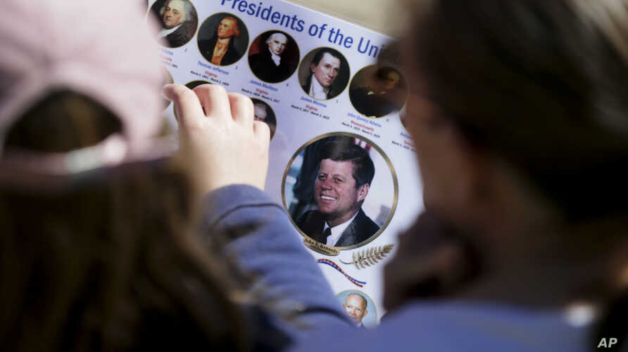 FILE - Michelle (R) and Matilda Chipperfield of England look at photos of U.S. Presidents while visiting Dealey Plaza in downtown Dallas, Oct. 25, 2017.