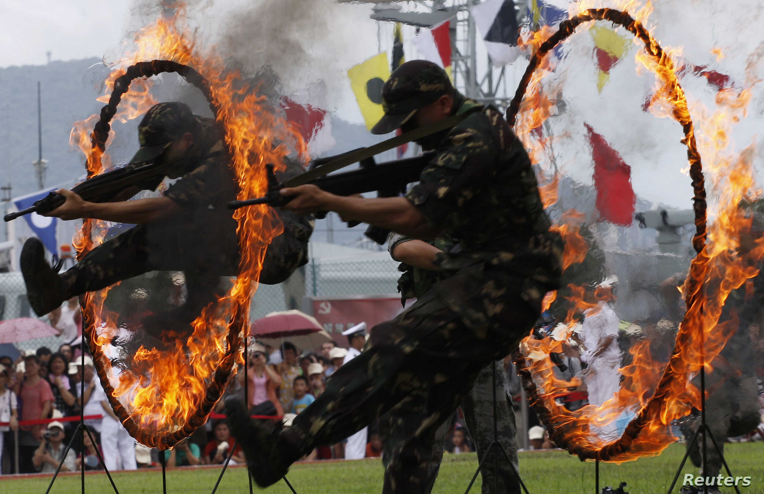Chinese People's Liberation Army (PLA) soldiers jump through rings of fire in a war game as part of the show for the public during an open day at the Ngong Shuen Chau Naval Base on Hong Kong's Stonecutters Island, July 28, 2012.