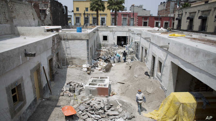 Masons work on restoring the building at 25 Manzanares Street, the oldest house in Mexico City, Sept. 10, 2018.