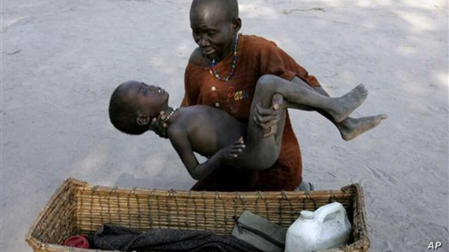 In this Dec. 21, 2005 file photo, a mother gently places her son in a basket as she takes him to a Medecins Sans Frontieres clinic after he contracted malaria, in Lankien, Southern Sudan. The fight against malaria is slowing down with a dramatic drop