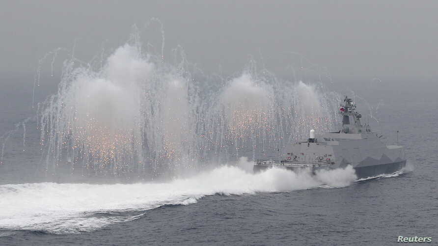 Flares are set off from a Taiwan navy missile ship in a military drill outside a naval base in Kaohsiung port, southern Taiwan, January 27, 2016.