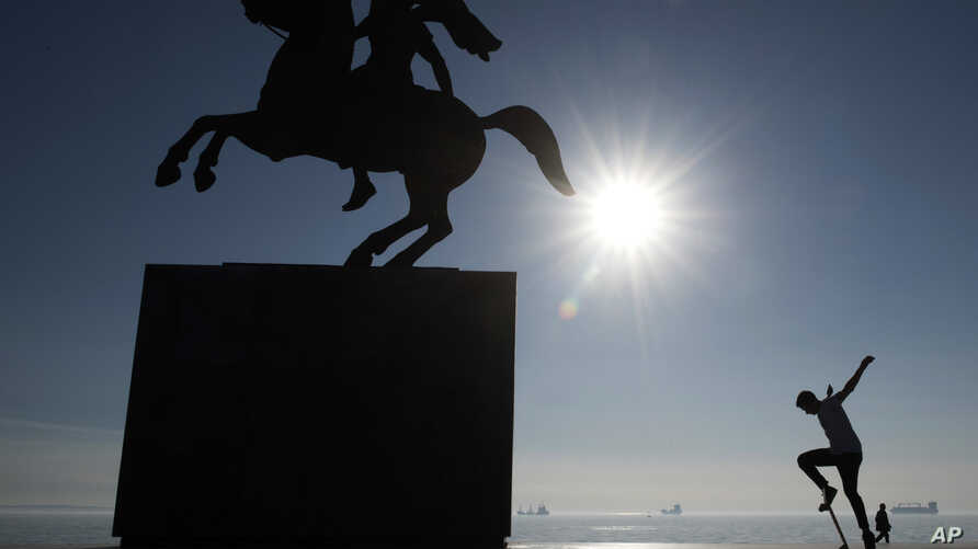 A skateboarder practices next to the modern bronze statue of Alexander the Great on his horse Bucephalus in the northern port city of Thessaloniki, Greece, Jan. 30, 2018. Parts of the city have been without water for five days because of a failed wat