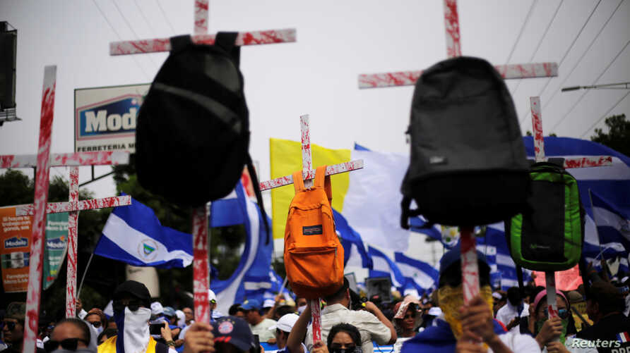 Demonstrators hold up crosses with backpacks during a march to demand the resignation of Nicaragua's President Daniel Ortega in Managua, Nicaragua, July 23, 2018.