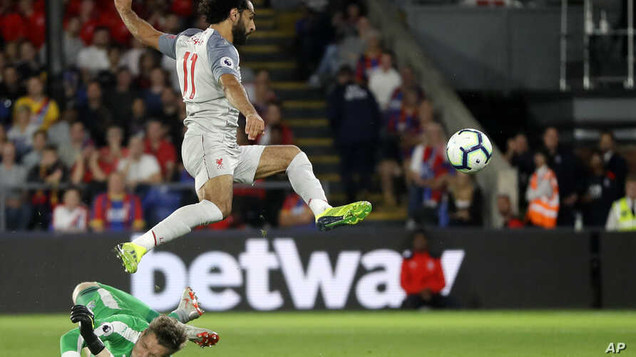 Crystal Palace's goalkeeper Wayne Hennessey, left, makes a save in front of Liverpool's Mohamed Salah during the English Premier League soccer match between Crystal Palace and Liverpool at Selhurst Park stadium in London, Monday, Aug. 20, 2018.