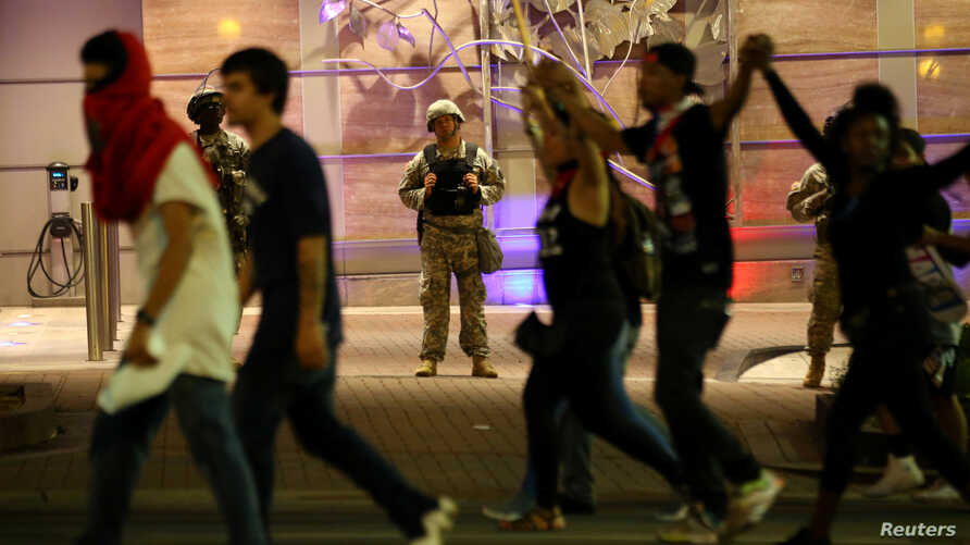 U.S. National Guard troops look on as people march through downtown to protest the police shooting of Keith Scott in Charlotte, North Carolina, U.S., September 22, 2016.