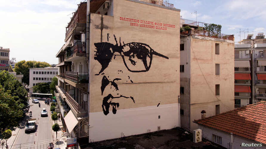 FILE - A giant mural depicts Italian composer Ennio Morricone created by Asterios Laskaris, Christos Laskaris and Dimitra Kalogirou under the auspices of the Greek Cultural Association Friends of Ennio Morricone's Music, in Larissa, Greece, July 24,