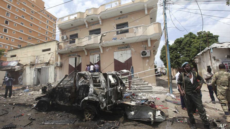 FILE - A Somali soldier stands on guard next to a destroyed car near a popular mall after a car bomb attack in Mogadishu, Somalia, July 30, 2017. The Somalia-based extremist group al-Shabab often carries out deadly bombings in Mogadishu.