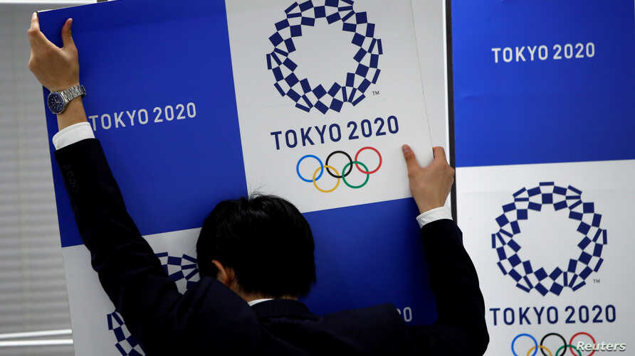 A staff takes out a banner featuring Tokyo 2020 Olympics emblem from the wall after a news conference hosted by International Olympic Committee (IOC) Vice President John Coates and President of Tokyo 2020 Olympic and Paralympic organising committee Y