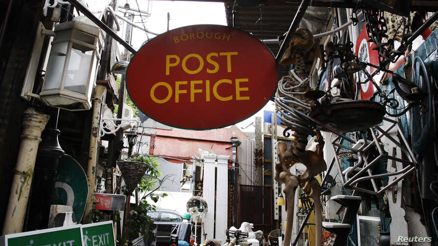 FILE - A sign for a Post Office hangs in an architectural rescue salvage shop alongside exit signs and light fittings in London, June 12, 2009. A Sky News report says a December 2018 cyberattack targeted the British Post Office, local government netw