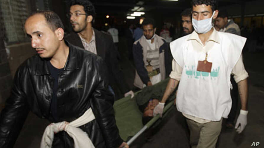 Medics carry an injured anti-government protester at a makeshift clinic outside Sana'a University, March 8, 2011