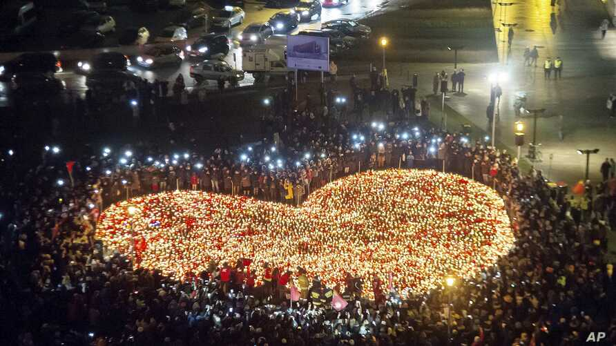 People create  a heart shaped with candles as a tribute to slain mayor of Gdansk Pawel Adamowicz in Gdansk, Poland,  Jan. 16, 2019.