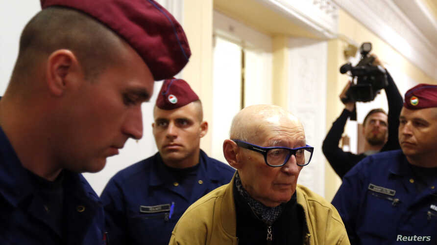 Former Communist Party official Bela Biszku is escorted by police during his trial in Budapest on May 13, 2014.