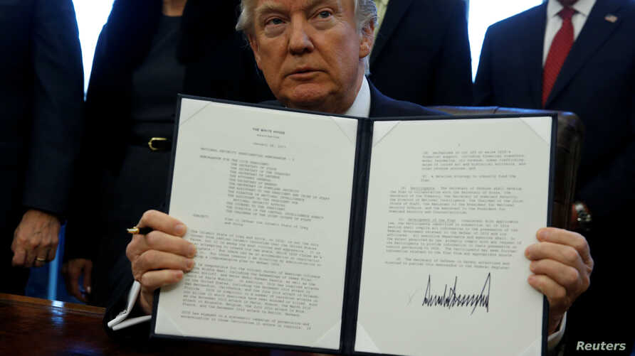 U.S. President Donald Trump signs a memorandum to security services directing them to defeat the Islamic State in the Oval Office at the White House in Washington, Jan. 28, 2017.