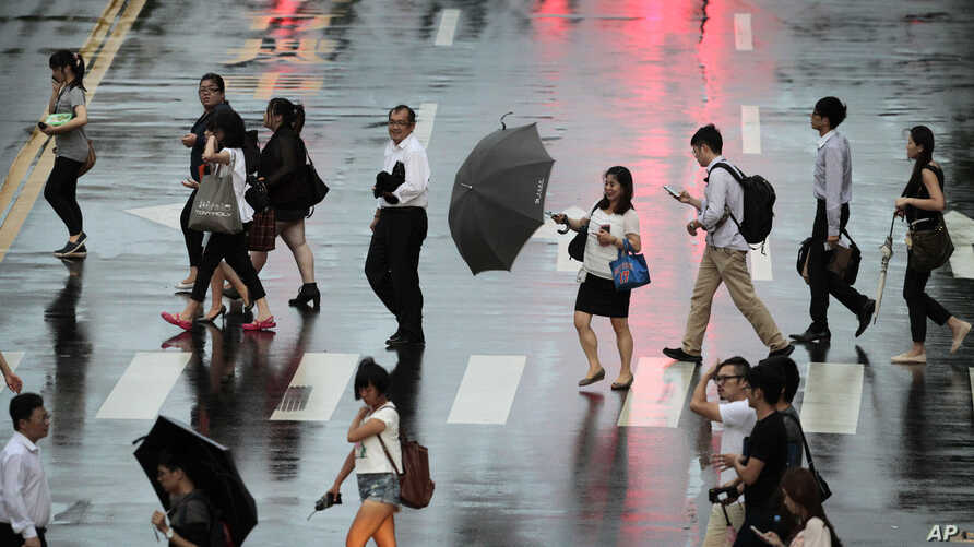 A woman struggles with her umbrella in strong winds and rain from approaching Typhoon Matmo in Taipei, July 22, 2014.