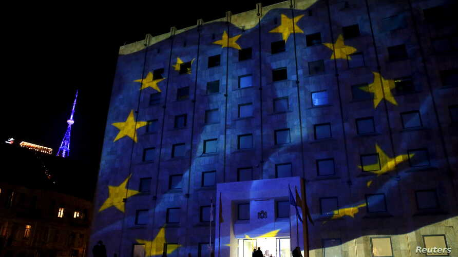 FILE - The European flag is projected on the government building as the TV tower is illuminated in blue in the background in Tbilisi, Georgia, December 18, 2015.