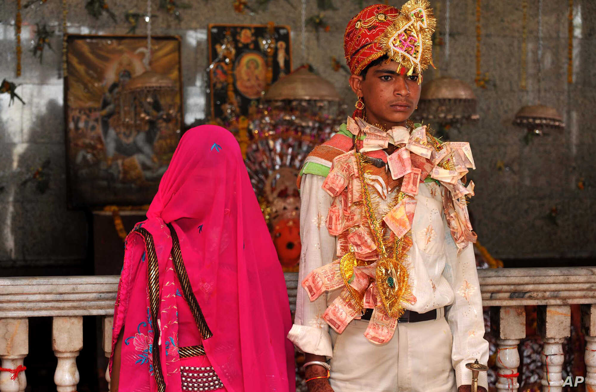 Newly wed Mamta Bai, 12, and her husband Bablu, 14, stands inside a temple in Rajgarh, about 155 kilometers (96 miles) from Bhopal, India, May 6, 2011.