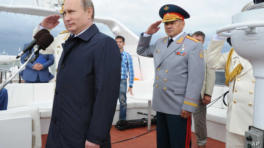 Russian President Vladimir Putin reviews a Navy parade in Baltisk, western Russia, July  26, 2015 during celebrations for Russian Navy Day. Defense Minister Sergei Shoigu stands at right.
