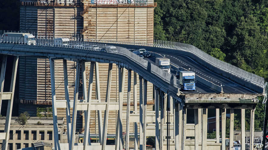 Cars and trucks are left on a section of the collapsed Morandi highway bridge in Genoa, northern Italy, Aug. 15, 2018.