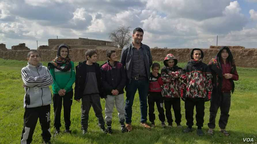 Some Yazidi children, who were recently freed from Islamic State, pose for a picture with their aid worker, near Hasaka, Syria, Feb. 27, 2019. (Jabber Jendo/VOA)