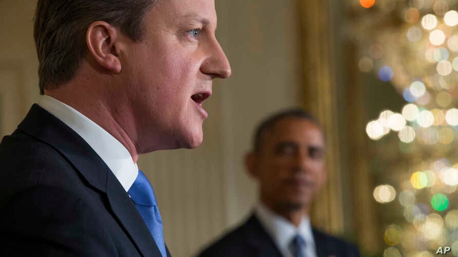 President Barack Obama listens as British Prime Minister David Cameron speaks during their joint news conference in the East Room of the White House, Jan. 16, 2015