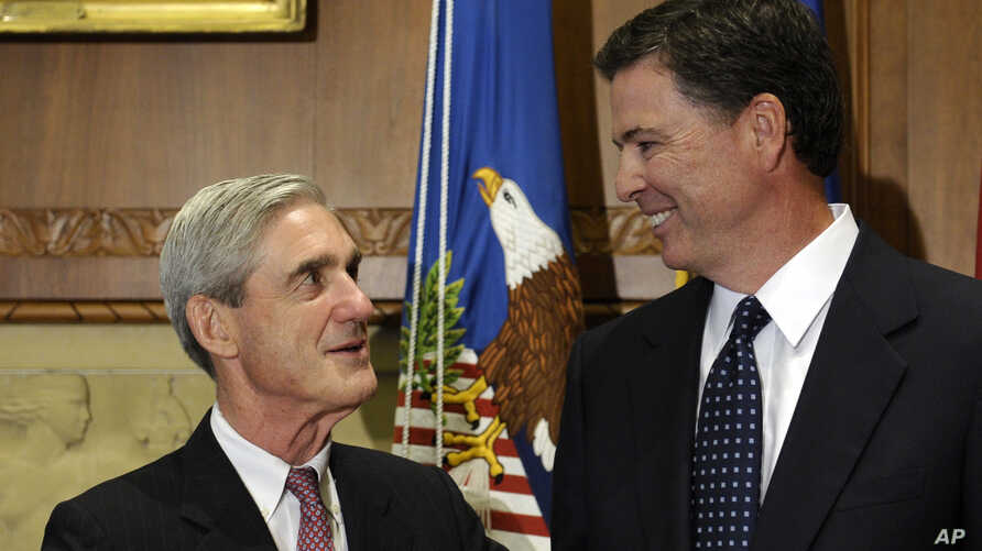 FILE - Former FBI Director James Comey talks with his predecessor, Robert Mueller, before Comey was officially sworn into office in Washington, Wednesday, Sept. 4, 2013.