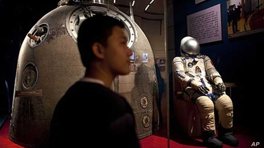 Visitor stands near the Shenzhou 5 re-entry capsule at an exhibition in Beijing, July 6, 2011.